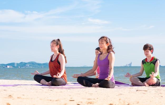 Aula de ioga na praia do mar no dia ensolarado, grupo de pessoas que faz pose de lótus com emoção relaxada