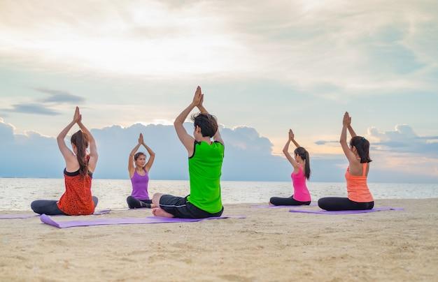 Aula de ioga na praia do mar no pôr-do-sol noturno, grupo de pessoas fazendo namaste poses