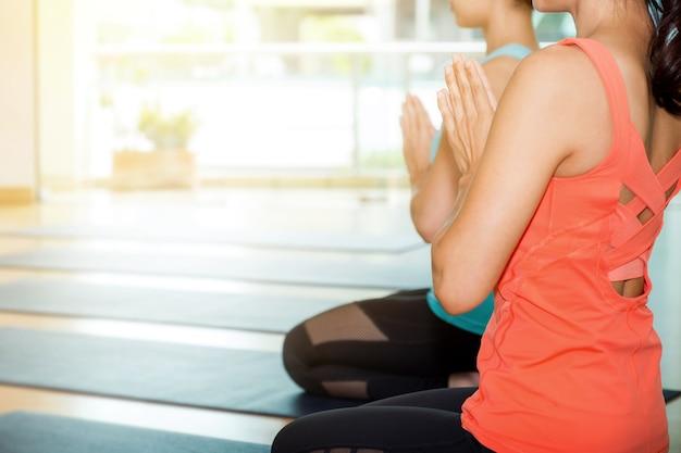 Aula de ioga na sala de estúdio, grupo de pessoas fazendo namaste pose com emoção relaxada