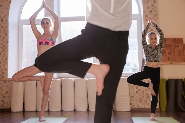 Aula de ioga para adolescentes. esporte para crianças. treino de meninas em foco em plano de fundo com instrutor feminino irreconhecível. estilo de vida familiar saudável, exercícios de alongamento