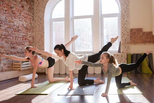 Aula de ioga para adolescentes. ginástica para meninas. crianças treinam junto com o treinador, plano de fundo do ginásio. estilo de vida saudável, exercícios de alongamento