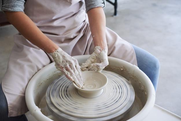 Aula de mestre em oficina de cerâmica para mulher fazendo prato de argila branca