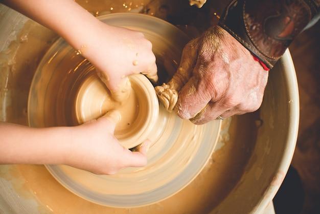 Aula de modelagem de argila na roda de oleiro na oficina de olaria