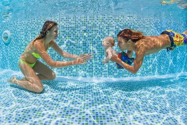 Aula de natação para crianças - bebê com mãe, pai aprendendo a nadar, mergulhando na piscina.