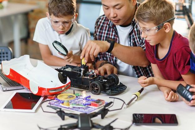 Aula de pesquisa em ciências físicas com um especialista asiático e três alunos praticando com modelo de carro controlado por rádio