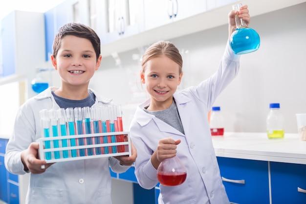 Aula de química. boas crianças inteligentes e positivas olhando para você e carregando reagentes químicos enquanto têm uma aula de química