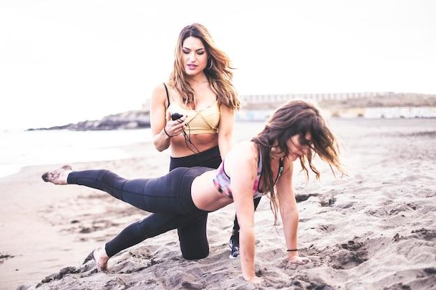 Aula de treinamento de fitness com personal trainer e jovem em posição de pilates na praia curtindo a natureza ao ar livre - estilo de vida saudável para as pessoas - céu claro e brilhante