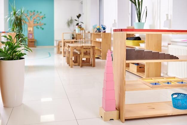 Aula leve no jardim de infância montessori. torre rosa feita de blocos
