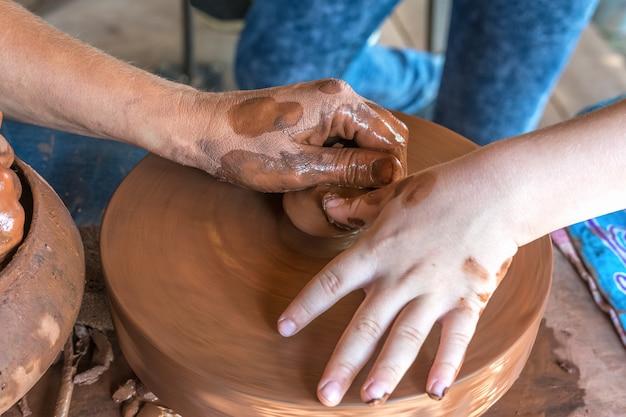 Aula magistral de cerâmica um oleiro ensina uma criança a fazer pratos de argila vermelha