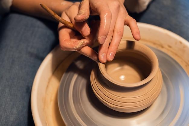 Aula na escola de cerâmica, esculpir um vaso, fechar plano.