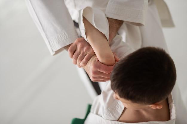 Aula particular de aikido. vista superior de um menino de cabelos escuros tendo aula particular de aikido com um treinador profissional