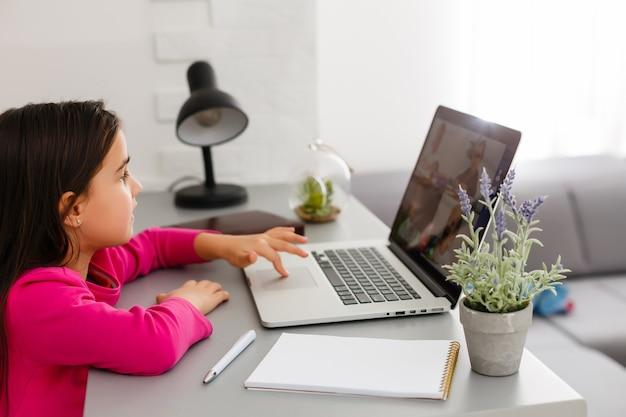 Aulas à distância. a criança sorri feliz e obtém conhecimento à distância. menina estudo online, aprendendo em casa com o laptop. escola online.