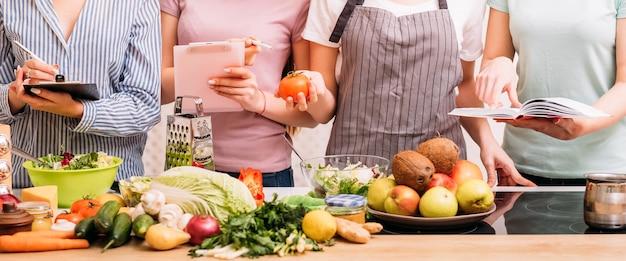 Aulas de cozinha. passatempo de preparação de alimentos. grupo de mulheres aprendendo estilo de vida alimentar saudável e nutrição equilibrada.