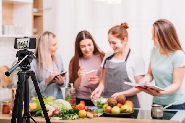 Aulas de culinária online. blogs de comida. grupo de mulheres preparando a refeição e filmando o tutorial em vídeo no celular.