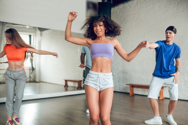 Aulas de dança. duas garotas atléticas e um rapaz dançando à tarde e gesticulando alegres