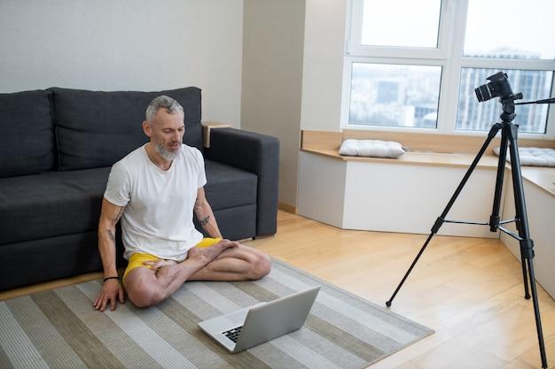 Aulas de ioga. um homem maduro de camiseta branca sentado no chão e gravando um tutorial de ioga online