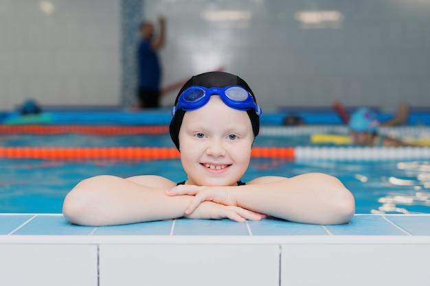 Aulas de natação para crianças na piscina - retrato de uma linda menina de pele branca em fato de banho e touca de natação