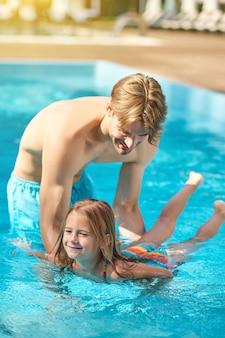 Aulas de natação. um jovem pai ensinando sua filha a nadar