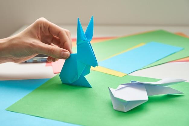 Aulas de origami. mulher faz origami coelho da páscoa de papel colorido. conceito diy