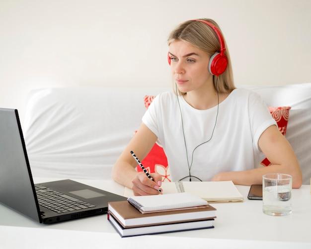 Aulas online com o aluno usando fones de ouvido vermelhos