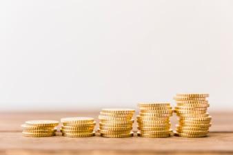 Aumentando moedas empilhadas na mesa de madeira