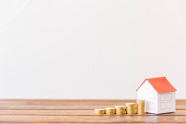 Aumentar moedas empilhadas perto de casa modelo na mesa de madeira