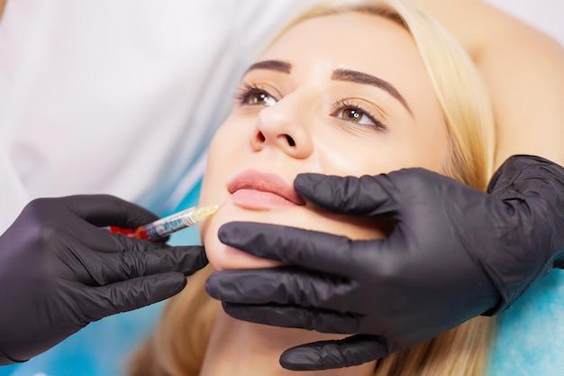 Aumento do lábio na clínica de cosmetologia. mulher bonita, recebendo injeção de beleza para os lábios.