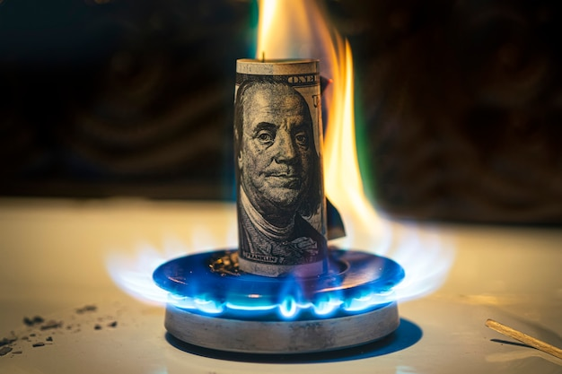 Aumento do preço do gás. conceito de problemas na economia dos eua. o dólar está queimando em um fogão a gás. a venda de gás. abastecimento caro de gás