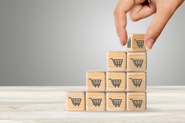 Aumento do volume de vendas para fazer um negócio crescer, cubo de madeira com símbolo de carrinho de compras.