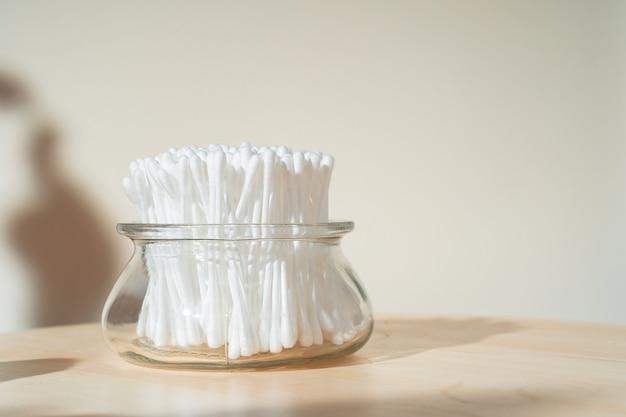 Auriculares de algodão higiênico em copo de vidro