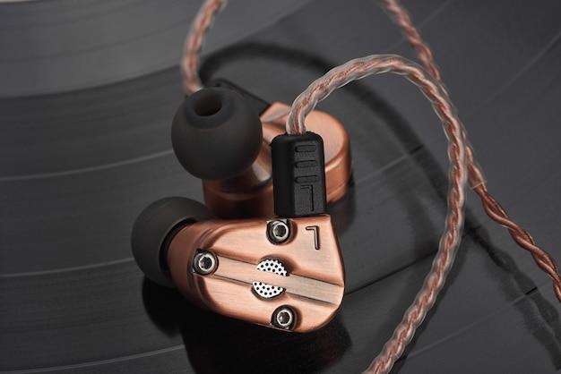 Auriculares de armadura equilibrada com driver dinâmico híbrido no disco de vinil lp.