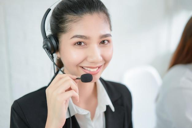 Auriculares vestindo de sorriso do microfone do consultante asiático de sorriso da mulher de negócios do operador do telefone do apoio ao cliente no local de trabalho.