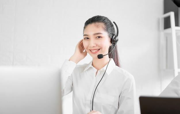 Auriculares vestindo do microfone do consultante asiático bonito da mulher do operador do telefone do apoio ao cliente no local de trabalho.