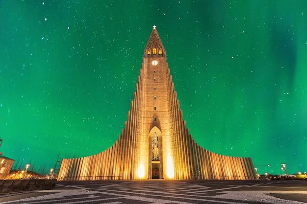Aurora boreal acima igreja hallgrimskirkja no centro da cidade de reykjavik, na islândia