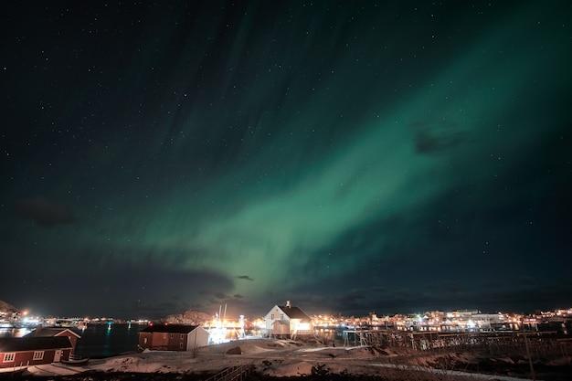 Aurora boreal, aurora boreal sobre uma vila escandinava na costa das ilhas lofoten, na noruega
