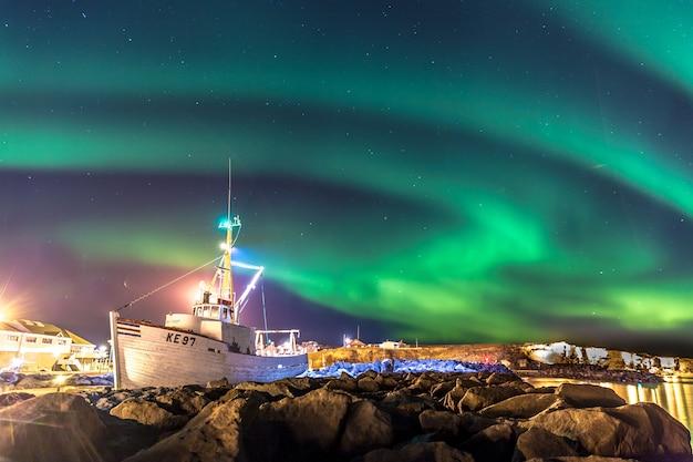 Aurora boreal colorida com um barco em primeiro plano na islândia