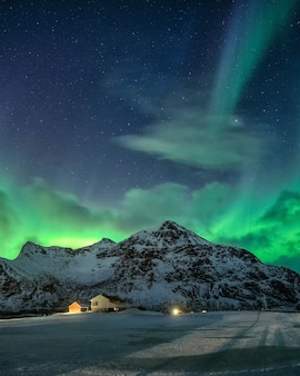 Aurora boreal com estrelado sobre a montanha nevada e vila nórdica à noite em flakstad, ilhas lofoten, noruega