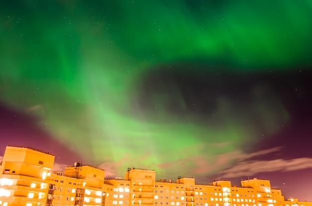 Aurora boreal é noite estrelada verde sobre a cidade e as casas.