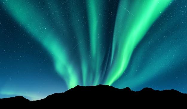 Aurora boreal e silhueta das montanhas