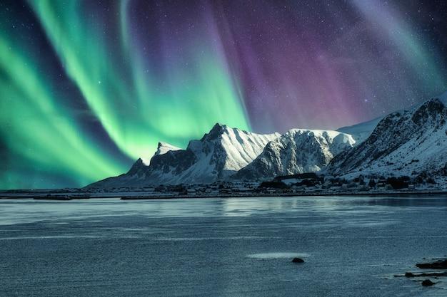 Aurora boreal, luzes do norte acima da montanha de neve nas ilhas lofoten