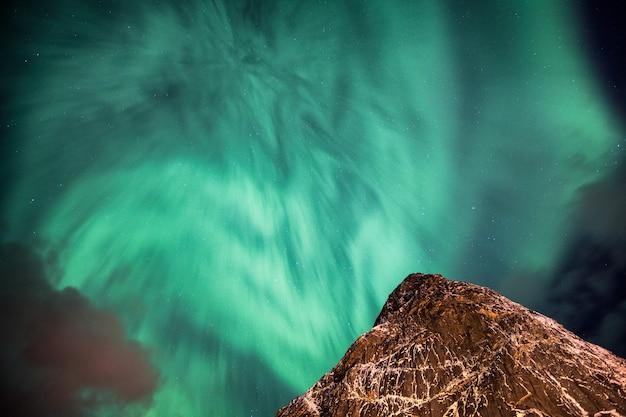 Aurora boreal (luzes do norte) dançando em uma montanha íngreme no céu noturno