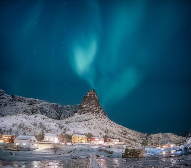 Aurora boreal na montanha de neve com vila de pescadores nas ilhas lofoten