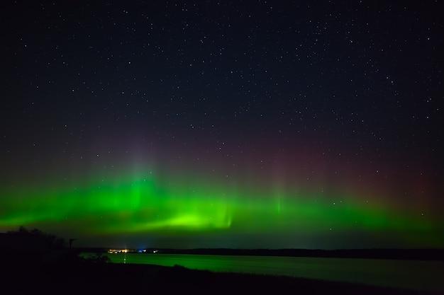 Aurora boreal sobre a cidade no litoral. luzes polares no céu estrelado à noite, sobre o lago.