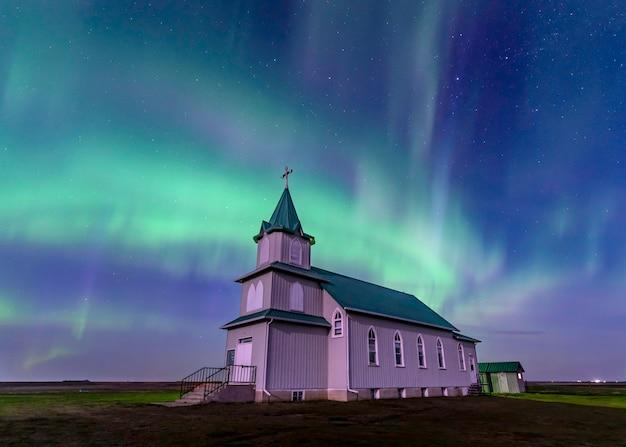 Aurora boreal sobre a histórica igreja luterana da paz em saskatchewan, canadá