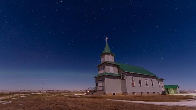 Aurora boreal sobre a histórica igreja luterana da paz nas pradarias em saskatchewan, canadá