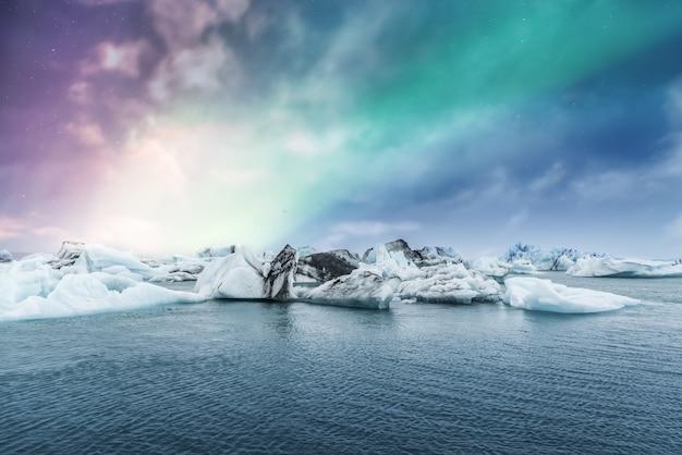 Aurora boreal sobre a lagoa de gelo da geleira de jokulsarlon na islândia