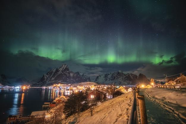 Aurora boreal sobre a luz da aldeia escandinava brilhando no inverno