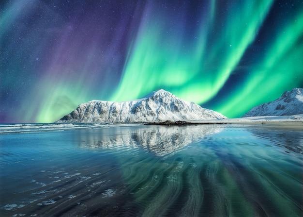 Aurora boreal sobre a montanha no inverno
