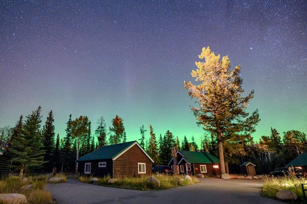 Aurora boreal sobre chalé de madeira no parque nacional