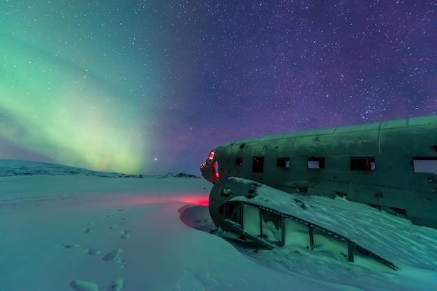 Aurora boreal sobre destroços de avião na islândia